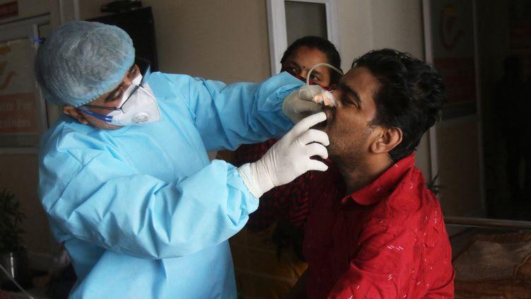 Un médecin indien examine la bouche d'un patient après une opération pour retirer une mucormycose dans un hôpital à Ghaziabad (Inde), le 3 juin 2021. (PANKAJ NANGIA / ANADOLU AGENCY / AFP)