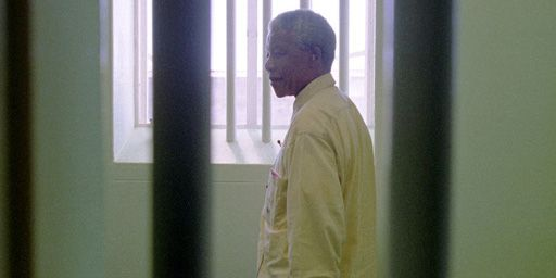 Le 11 février 1994,dans la prison de Robben Island,Nelson Mandela regarde par la fenêtre de la cellule où il a été incarcéré pendant la majeure partie de sa détention. Une détention qui a duré 27 ans. Le matricule 46664 a été définitivement libéré le 11 février 1991. A l'âge de 71 ans. (Reuters - Patrick de Moirmont)