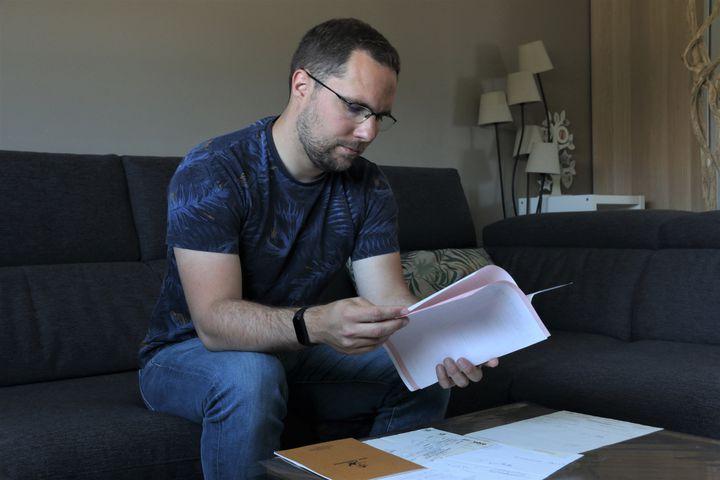 Alexandre Mercier regarde à son domicile les documents de ses parents concernant le don dont il est issu, le 31 mai 2021près de Douai (Nord). (VALENTINE PASQUESOONE / FRANCEINFO)