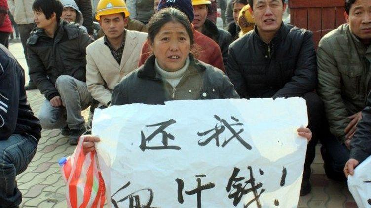 Des travailleurs migrants chinois s'agenouillent pour réclamer des impayés de salaire,lors d'une manifestationsur une place de Weinan, ville au nord-ouest de la province du Shaanxi, le 10 janvier 2013. (Mu caiyuan / Imaginechina)