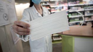 Une pharmacienne tend un masque à Périgueux. Illustration. (ROMAIN LONGIERAS / HANS LUCAS)
