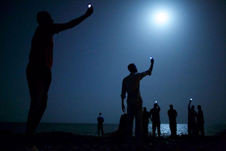 Des migrants africains brandissent leurs téléphones sur une plage de Djibouti, février 2013. (JOHN STANMEYER / VII FOR NATIONAL GEOGRAPHIC)
