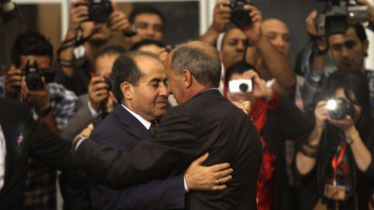 Le président du CNT, Moustafa Abdel Djalil (à droite) serre la main de Mahmoud Jibril, Premier ministre libyen pendant la guerre, après la passation de pouvoir à l'Assemblée, le 8 août 2012 à Tripoli (Libye). (ESAM AL-FETORI / REUTERS)