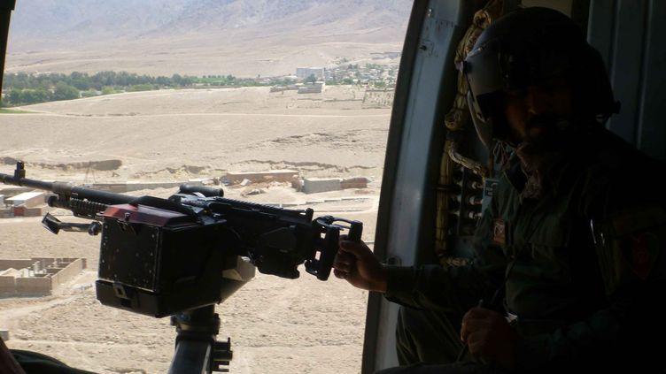 Depuis un hélicoptère, un soldat afghan scrute la province deNangarhar, le 8 août 2016, oùle chef de l'Etat islamique,Hafez Saïf, a été tué. (ZABIHULLAH GHAZI / AFP)