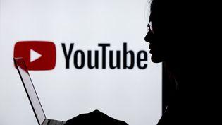 Une femme utilise un ordinateur devant un logo Youtube, le 18 juillet 2018, à Ankara, en Turquie. (AYTAC UNAL / ANADOLU AGENCY / AFP)