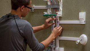Un futur électricien réalise un exercice à l'Université Régionale des métiers de l'artisanat à Arras (Pas-de-Calais), le 26 septembre 2014. (PHILIPPE HUGUEN / AFP)