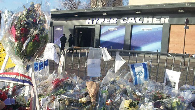 (Devant l'Hyper Cacher des habitants du quartier continuent à entretenir les milliers de fleurs et bougies deposés en hommage aux victimes © Radio France / Jérôme Jadot)