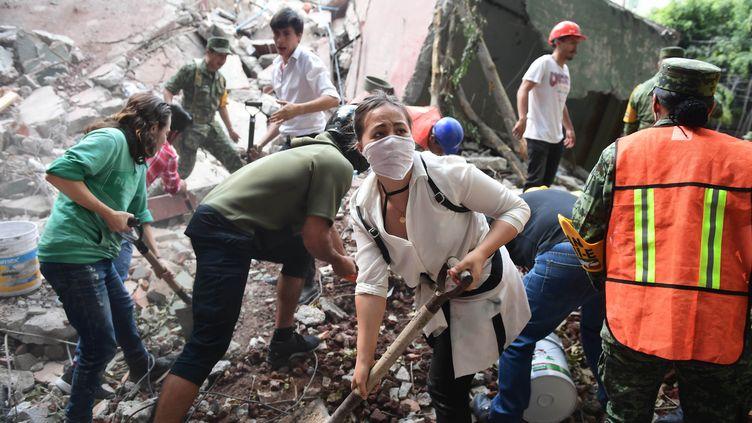 Des habitants de Mexico (Mexique) fouillant les décombres d'un immeuble effondré, le 19 septembre 2017. (RONALDO SCHEMIDT / AFP)