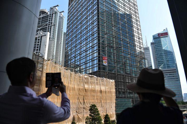 La banderole d'Alain Robert,accrochée sur un gratte-ciel du quartier des affaires de Hong Kong, le 16 août 2019. (LILLIAN SUWANRUMPHA / AFP)