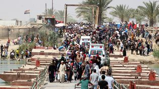 Des résidents irakiens de la ville de Ramadi, qui ont fui les jihadistes, attendent pour traverser le pontBzibez, à la frontière sud-ouest de Bagdad, le 20 mai 2015. (SABAH ARAR / AFP)