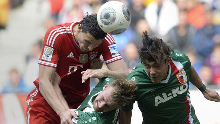 Le défenseur du Bayer Munich Daniel Van Buyten face aux joueurs d'Ausbourg (CHRISTOF STACHE / AFP)