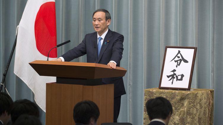 Le secrétaire général du Cabinet, Yoshihide Suga, annonce le nom de la nouvelle ère impériale, lors d'une conférence de presse, à Tokyo (Japon), le 1er avril 2019. (KAZUHIRO NOGI / AFP)