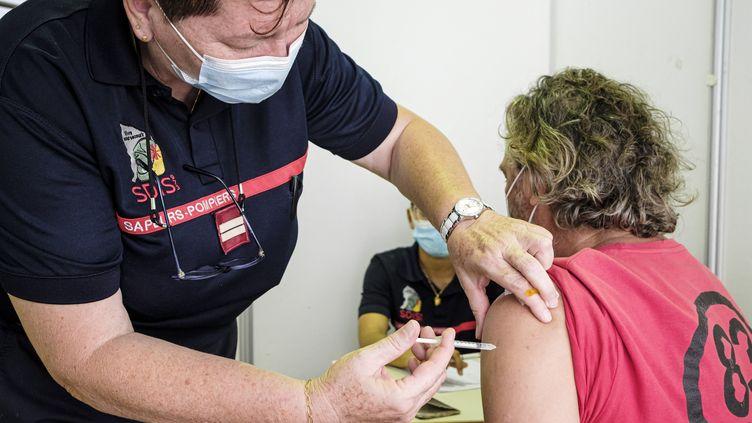 Un pompier injecte une dose de vaccin contre le Covid-19 dans un centre de Cayenne (Guyane), le 30 mars 2021. (JODY AMIET / AFP)