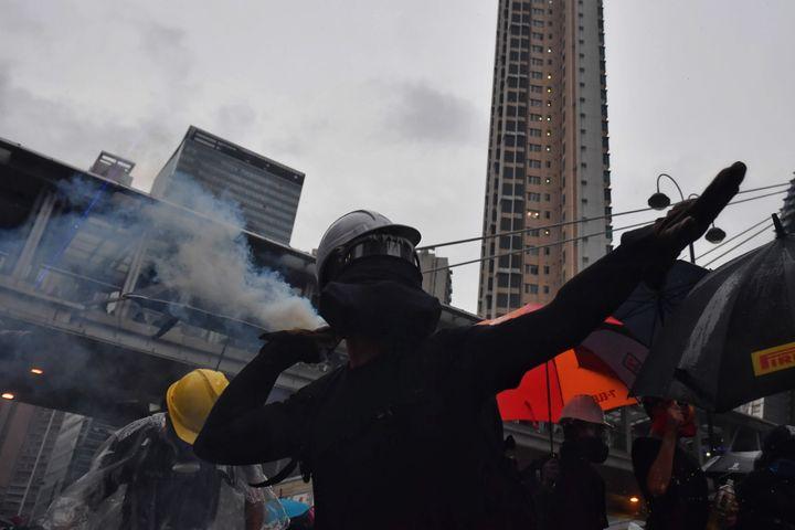 Un manifestant lance un projectile en direction des forces de l'ordre à Hong Kong, le 25 août 2019. (LILLIAN SUWANRUMPHA / AFP)