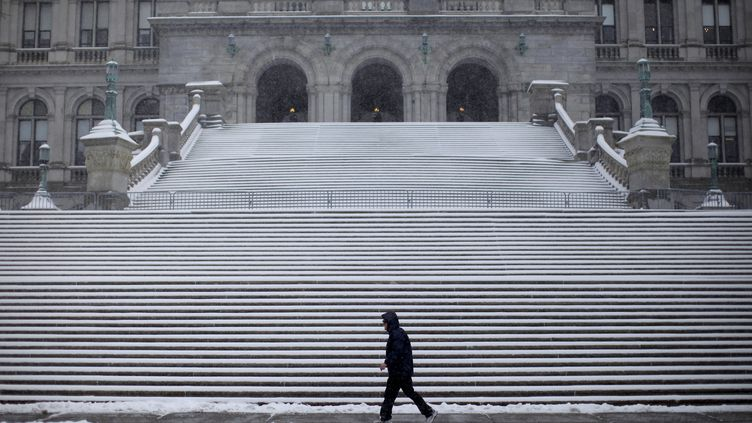 Un homme marche dans la ville d'Albany (Etats-Unis), ville où le gourou Keith Raniere abasé son organisation NXIVM. (MIKE SEGAR / REUTERS)