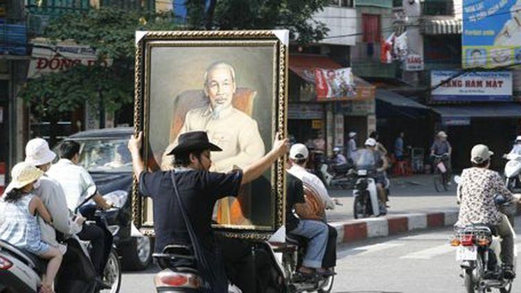 Dans une rue d'Hanoï, capitale du Vietnam, un motocycliste transporte un portrait de l'ancien dirigeant révolutionnaire, Ho Chi Minh (12 juin 2007). (Reuters - Kham)