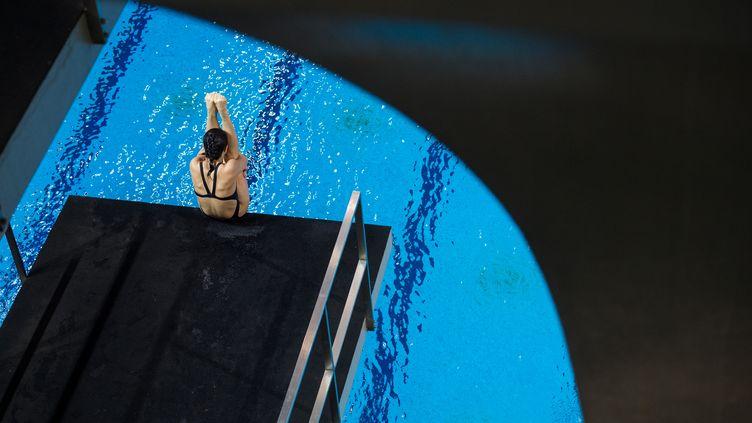 Un membre de l'équipe nationale chinoise de plongeon s'entraîne sur un plongeoir de 5 mètres à Shangai, en Chine, le 20 janvier 2016. (JOHANNES EISELE / AFP)