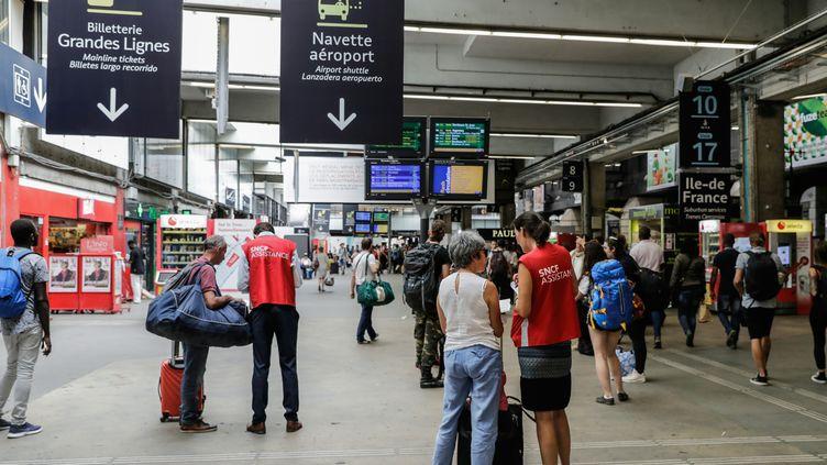 Des voyageurs à la gare Montparnasse à Paris, le 27 juillet 2018. (THOMAS SAMSON / AFP)