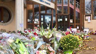 Fleurs, messages et bougies sont déposées devant l'entrée du collègedu Bois d'Aulne, à Conflans-Sainte-Honorine, le 30 octobre 2020, deux semaines aprèsl'assasinat du professeur d'histoire-géographieSamuel Paty, (KACHANER ALICE / RADIO FRANCE)