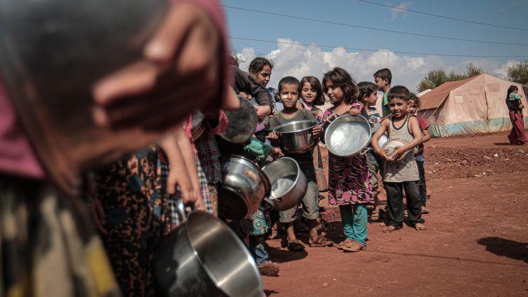Des enfants font la queue pour recevoir de la nourriture à Idleb, en Syrie, le 7 octobre 2019. (MUHAMMED SAID / ANADOLU AGENCY / AFP)