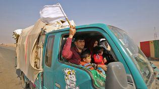Un Irakien agite un drapeau blanc de sa voiture, à 40 kilomètres de Mossoul (Irak), alors qu'il fuit la région avec sa famille à l'approche des forces gouvernementales. (AHMAD AL-RUBAYE / AFP)