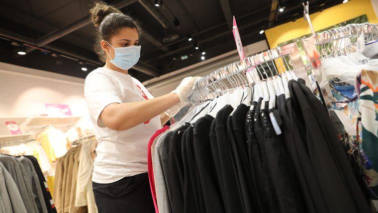 Une employée d'un centre commercial de Corbeil-Essonnes portant un masque prépare le magasin en vue de sa réouverture, le 11 mai, photographiée le 7 mai 2020. (ARNAUD JOURNOIS / MAXPPP)