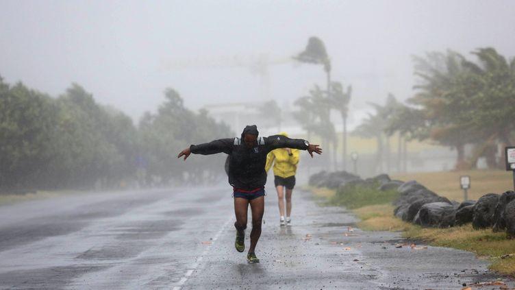Un homme affronte les vents violents de Bejisa, à La Réunion, le 2 janvier 2014. (RICHARD BOUHET / AFP)