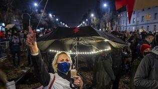 Une manifestante pro-IVG brandit un cintre, un symbole des avortements illégaux, devant la résidence deJaroslaw Kaczynski, le leader du parti ultra-catholique PiS (Droit et Justice), à Varsovie (Pologne), le 30 octobre 2020. (WOJTEK RADWANSKI / AFP)