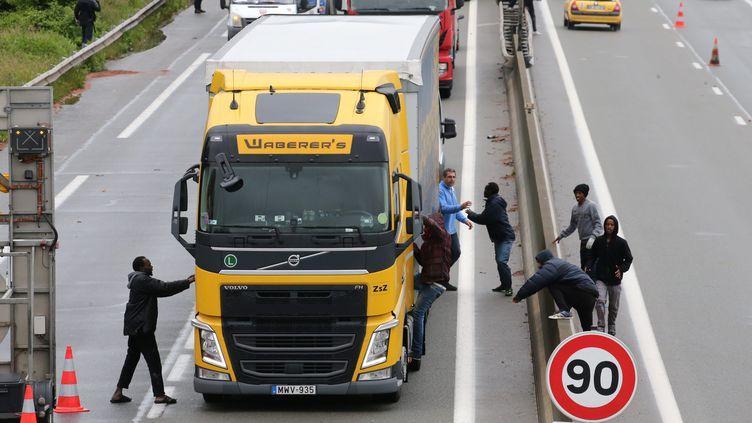 Des migrants tentent de pénétrer dans un camion en direction de l'Angleterre, le 20 juin 2016 à Calais. (MAXPPP)