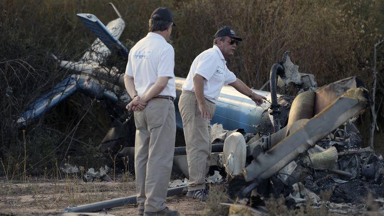 """Des enquêteurs argentins autour de la carcasse d'un des hélicoptères qui se sont écrasés lors du tournage de l'émission """"Dropped"""" àVilla Castelli (Argentine), le 10 mars 2015. (JUAN MABROMATA / AFP)"""