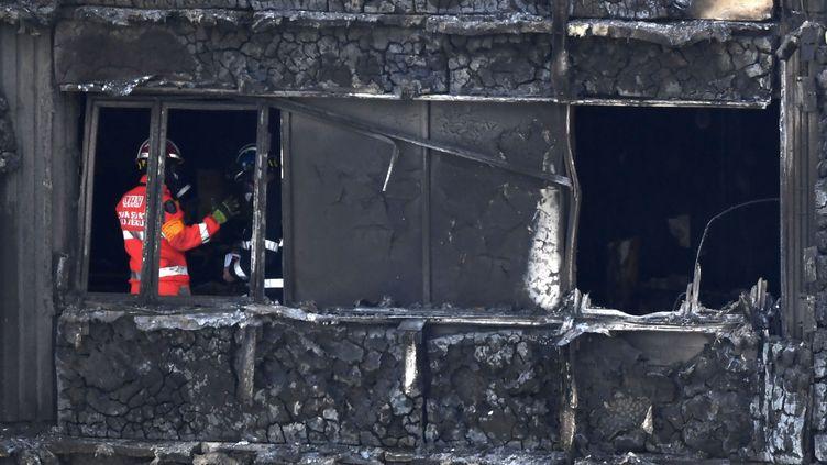 Des pompiers et des policiers inspectent l'intérieur de la tour Grenfell, le 16 juin 2017, à Londres. (CHRIS J RATCLIFFE / AFP)