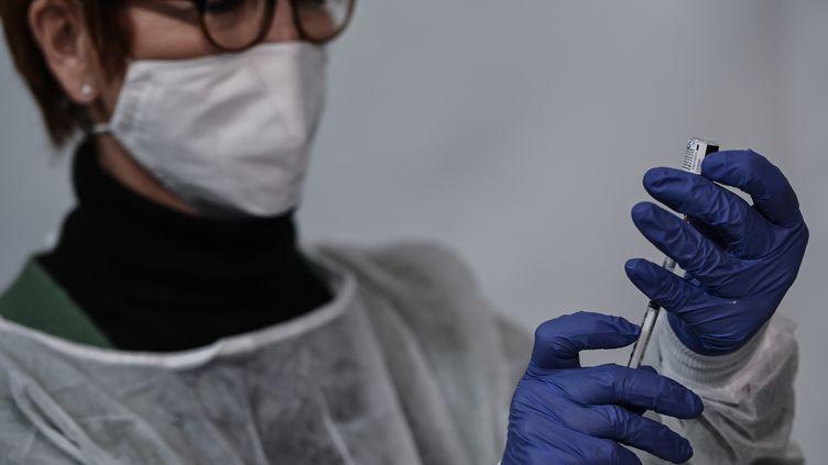 Une soignante prépare un vaccin contre Covid-19, au Palais des Sports de Lyon, le 14 janvier 2021. Photo d'illustration. (JEAN-PHILIPPE KSIAZEK / AFP)