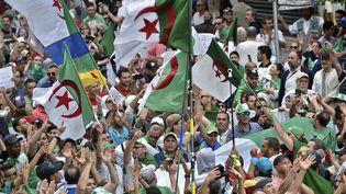 Les manifestants algériens agitent des drapeaux nationaux lors d'une manifestation antigouvernementale devant le Grande-Poste à Alger, le 24 mai 2019. (RYAD KRAMDI / AFP)