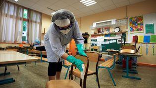Une membre du personnel désinfecte une salle de classe avant la réouverture d'une école primaire à Toulouse (Haute-Garonne), le 6 mai 2020. (ALAIN PITTON / NURPHOTO / AFP)