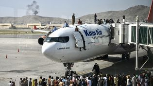 Des Afghans grimpent sur un avion, à l'aéroport de Kaboul (Afghanistan), le 16 août 2021. (WAKIL KOHSAR / AFP)