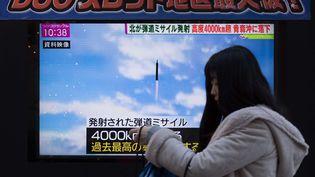 Une femme passe devant une télévision montrant des images du missile nord-coréen, le 29 novembre 2017 à Tokyo (Japon). (DELETREE/SIPA)