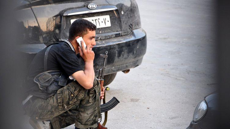 Un rebelle syrien passe un coup de fil après avoir pris position à Alep, dans le nord de la Syrie, le 31 juillet 2012. (PIERRE TORRES / AFP)