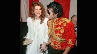 Michael Jackson porte son fameux gant à cristaux noirs, en compagnie de l'actrice Brook Shields, le 16 janvier 1984 aux American Music Awards.  (DOUG PIZAC/AP/SIPA)