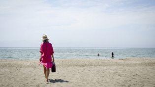 Une femme se promène sur la plage deBeauduc, dans les Bouches-du-Rhône, le 6 août 2009. (ALICE BEUVELET / HANS LUCAS / AFP)