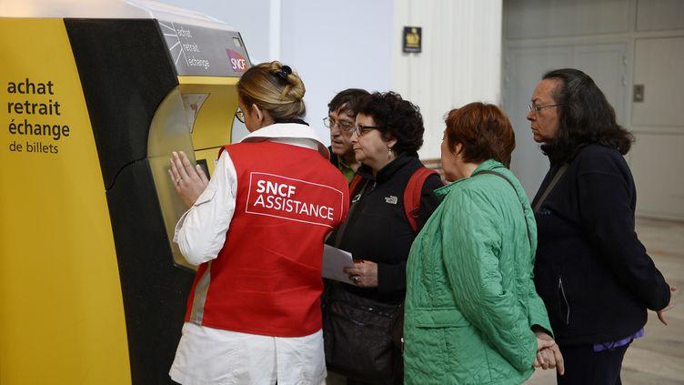 Une employée de la SNCF aide des voyageurs lors d'une grève, à la gare d'Austerlitz, à Paris, le 19 juin 2014. (STEPHANE DE SAKUTIN / AFP)