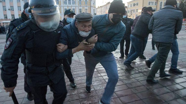 Des policiers arrêtent un homme lors d'une manifestation en soutien à l'opposant Alexeï Navalny, àOulan-Oudé, en Russie, le 21 avril 2021. (ANNA OGORODNIK / AP)