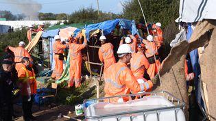 """Des ouvriers démontent les cabanes de la """"jungle"""" de Calais (Pas-de-Calais), le 25 octobre 2016. (DENIS CHARLET / AFP)"""