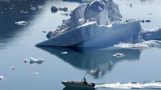 Un pêcheur parmi un pack d'iceberg dans un fjord, près de Tiniteqilaaq, au Groenland, le 5 juillet 2020. (PHILIPPE ROY / AFP)