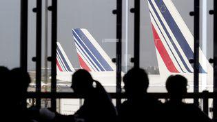 Des passagers dans un café de l'aéroport d'Orly, le 15 septembre 2014, tandis que l'on aperçoit des avions Air France par la votre. (KENZO TRIBOUILLARD / AFP)