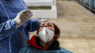 Un médecinprélèveun échantillon sur une femme pour des tests Covid-19 dans une rue du gouvernorat de l'Ariana, à 6 km de la capitale Tunis, le 8 janvier 2021. (CHEDLY BEN IBRAHIM / NURPHOTO)
