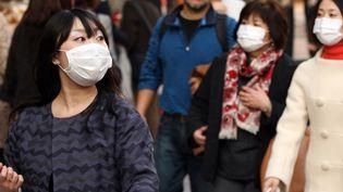 Des piétons dans une rue de Wuhan, ville chinoise au cœur de l'épidémie du nouveau coronavirus, le 26 janvier 2020. (HITOSHI YAMADA / NURPHOTO / AFP)