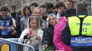 Des participants patientent à l'entrée du Circus, une boîte de nuit de Liverpool (Royaume-Uni), où est organisée une soirée-test pour évaluer le risque de contaminations, le 30 avril 2021. (PETER BYRNE / PA / AP)
