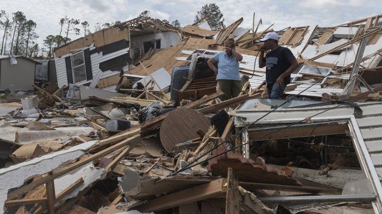 Un coupledevant son mobile home détruit après le passage de l'ouragan Laura à Lake Charles, en Louisiane, le 27 août 2020. (ANDREW CABALLERO-REYNOLDS / AFP)