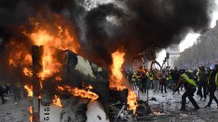 Un manifestant jette un vélo dans les flammes alors qu'une remorque brûle sur les Champs-Elysées. (BERTRAND GUAY / AFP)