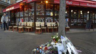Des bougies et des fleurs devant Le Comptoir Voltaire, où s'était fait exploser un kamikaze lors des attentats, le 16 décembre 2015. (BERTRAND GUAY / AFP)